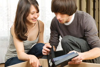 Couple looking at VHS video tapes to transfer to DVD
